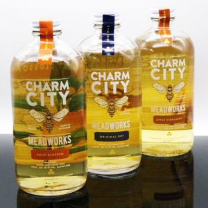 Three bottles of Charm City Meadworks mead with label visible through the clear bottle